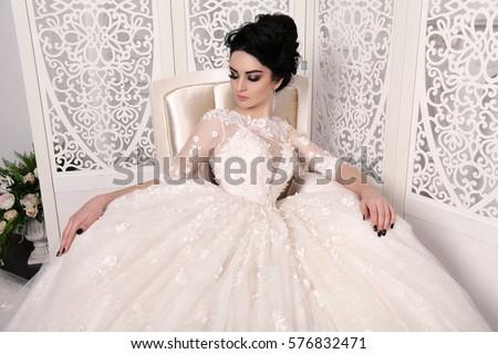 fashion studio photo of gorgeous bride with dark hair in luxurious wedding dress