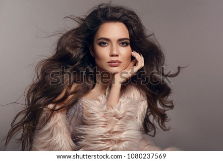 Fashion studio photo of gorgeous sexy brunette woman with long healthy hair and evening makeup posing with pink fur coat isolated on gray background. Fashionable girl portrait. Vogue style.