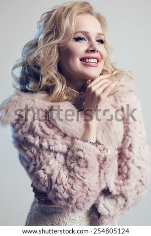 fashion studio photo of gorgeous woman with blond hair wearing  luxurious fur coat  and elegant dress