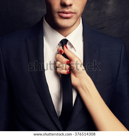 fashion studio photo of sexy impassioned couple. handsome businesslike man in glasses,woman\'s hand holding his tie