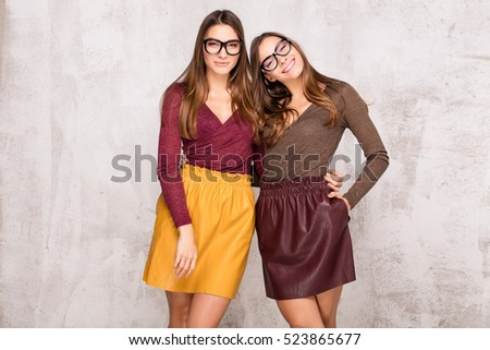 Fashion studio photo of two beautiful young girls . Beauty portrait of twins sisters. Perfect face makeup. Smiling happy ladies.