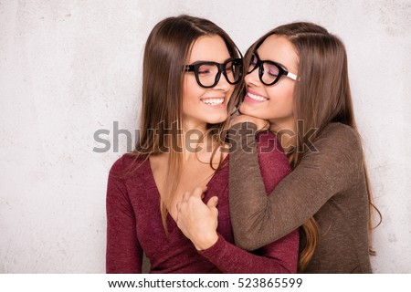 Fashion studio photo of two beautiful young girls having fun together. Beauty portrait of twins sisters. Perfect face makeup. Smiling happy ladies.