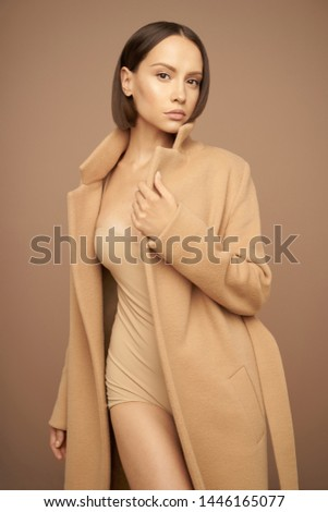 Fashion studio photo of young beautiful lady in beige coat on beige background. Total beige. Fashion look book. Warm Autumn. Warm Spring #1446165077