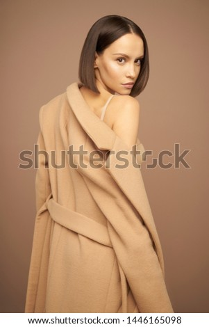 Fashion studio photo of young beautiful lady in beige coat on beige background. Total beige. Fashion look book. Warm Autumn. Warm Spring #1446165098