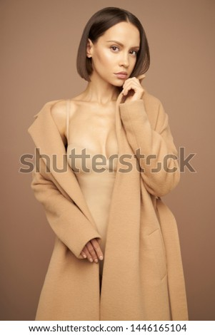 Fashion studio photo of young beautiful lady in beige coat on beige background. Total beige. Fashion look book. Warm Autumn. Warm Spring