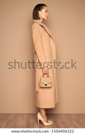 Fashion studio photo of young beautiful lady in beige coat on beige background with little handbag. Total beige. Fashion look book. Warm Autumn. Warm Spring
