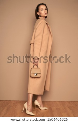 Fashion studio photo of young beautiful lady in beige coat with little handbag on beige background. Total beige. Fashion look book. Warm Autumn. Warm Spring
