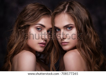 Fashion studio picture of two twins beautiful women. Close-up beauty portrait of sisters models