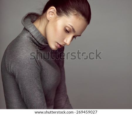 Fashion studio portrait of a young sensual brunette model in gray roll neck jumper. Looking down.