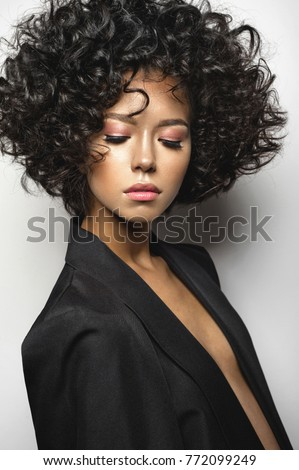 Fashion studio portrait of beautiful woman in black cape with afro curls hairstyle. Fashion and beauty #772099249