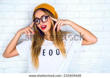 Fashion studio portrait of pretty young hipster blonde woman with bright sexy make up and glasses , wearing stylish urban t shirt and hat, White urban wall background.  #232604668
