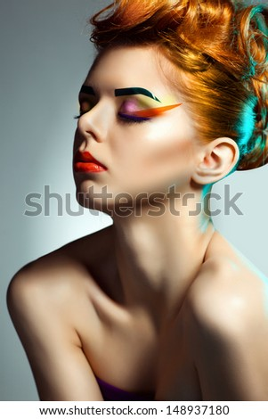 Fashion studio shot of beautiful  woman in violet dress with  Professional makeup and hairstyle