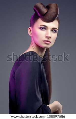 Fashion studio shot  of beautiful woman with a luxurious and healthy hair on natural background. Professional makeup and hairstyle
