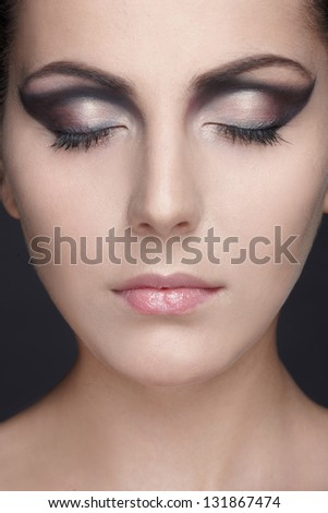 Fashion studio shot of beautiful young woman with make-up. Close-up portrait.