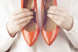 Fashion studio shot of shopping girl holding a red  high heel shoe in her hand on a light background.