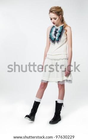 Fashion style - beautiful brunette slim girl in white dress posing on podium