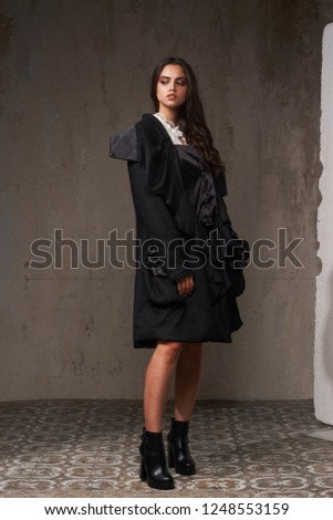 Fashion style full length portrait of young beautiful brunette with long wavy hair. Pretty woman in black rain coat posing and astanding over gray stone wall #1248553159