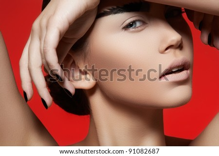 Fashion style, manicure, cosmetics and make-up. Profile portrait of beautiful woman with creative strong eyebrows makeup, clean skin, cheekbones and dark manicure on bright red background