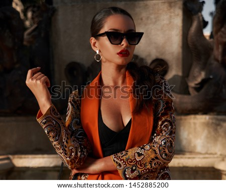 Fashion style outdoor portrait. Elegant woman in colorful orange suit with black handbag standing and posing against fountain in old town on a sunny evening, Sunny evening. Tropical city #1452885200
