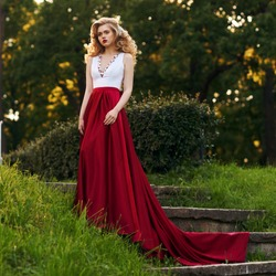 Fashion style photo of young beautiful woman in evening dress with white top and red flying skirt posing in summer park at sunset under green trees and close to old brick tower