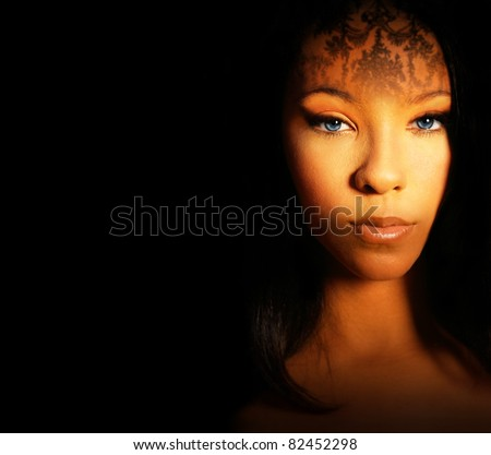 Fashion style portrait of a beautiful female model with exotic makeup and dark background with lots of copy space