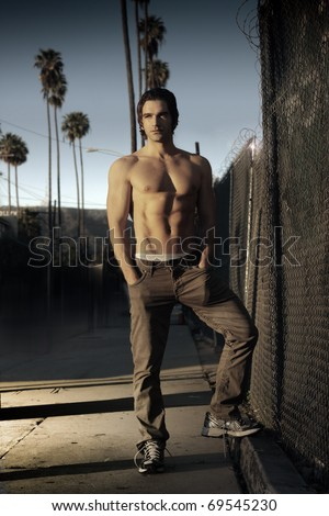 Fashion style portrait of a classic California guy outdoors with golden sunset light and palm trees in the distance