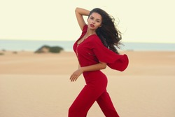 Fashion style portrait of young beautiful tall slim female model posing in red overall at sand beach. Outdoor summer portrait with soft evening light