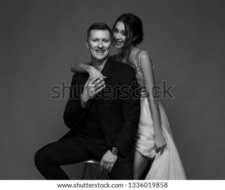 Fashion style studio portrait of young adult couple. Pretty sexy lady in luxury elegant evening dress standing near man in black suit sitting on high chair. #1336019858