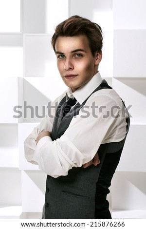 Fashion style studio portrait of young successful man dressed in stylish classic clothes with necktie with crossed arms and looking in camera