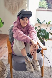 Fashion stylish hipster teen girl pink hair wear vr glasses headset hold controller sit in chair at home look at camera. Digital innovation video gaming, virtual reality 3D 360 apps. Vertical portrait