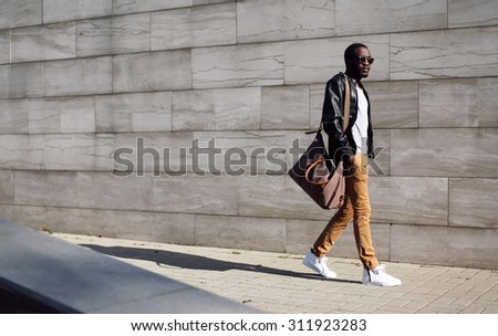 Fashion stylish young african man in sunglasses and black rock leather jacket with bag walking over grey textured city background