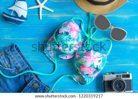 Fashion summer swimsuit bikini, sunglasses and big hat, vintage old camera Summer bikini and accessories stylish outfit beach set. Ocean sea vacation, top view.  Summer Concept