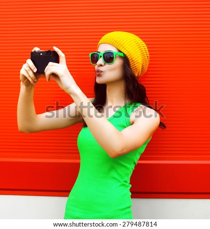 Fashion, summer, technology and people concept - pretty cool girl in sunglasses makes self-portrait on the camera outdoors against colorful red wall