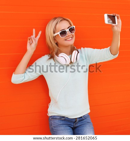 Fashion, technology and people concept - happy smiling pretty girl makes self-portrait on the smartphone in sunglasses with headphones against colorful orange wall