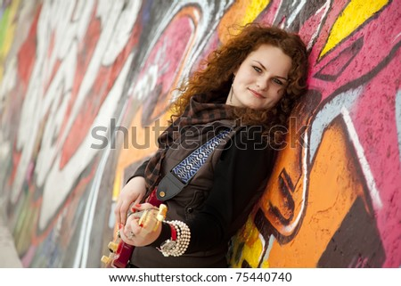 Fashion teen girl with guitar at graffiti background.