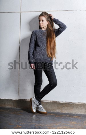 Fashion teenager girl standing leaning back against a white concrete wall. Stylish attractive hipster girl 12 years posing raising hand up holding hair. Beautiful model tests. Series of photos. #1221125665