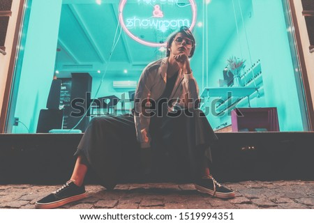 Fashion tomboy teen hipster short hairstyle gen z girl wear stylish clothes glasses sitting on street near neon sign, female model woman look at camera in city night light 80s style glow, portrait