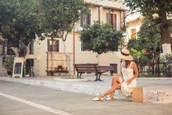 Fashion tourist woman in hat sitting on the city street. Summer wanderlust. Crete, Greece