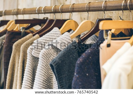 Fashion trend concept. Warm winter ladies clothes collection with knitted wool jumpers on wooden hangers. #765740542