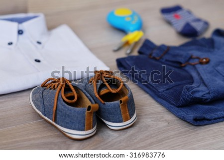 Fashion trendy look of baby clothes and toy on the wooden floor, baby fashion concept. Little boy clothes set.
