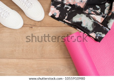 Fashion trendy trainers and leggings, pink yoga mat. Hipster Set. Female sneakers, sport shoes in flat lay style, top view. Fitness concept, active lifestyle, body care concept. Wood Background