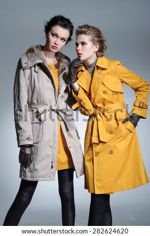 fashion two model in coat clothes posing on light background