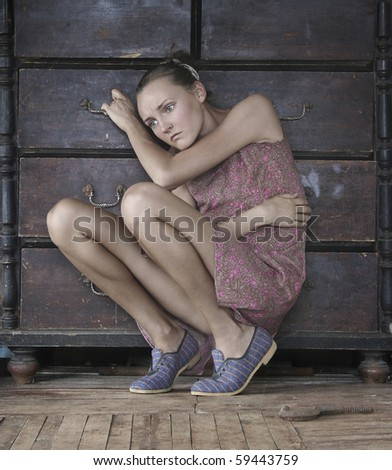 Fashion type photo of an attractive young woman sitting near an old chest of drawers