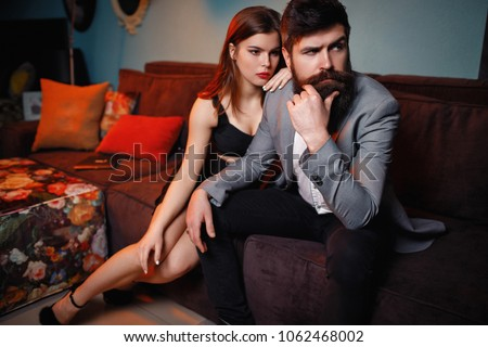 Fashion unhappy couple sitting on couch after quarrel fight thinking of break up or divorce, bearded upset man and beautiful woman not talking having conflict, bad relationships concept, close up view