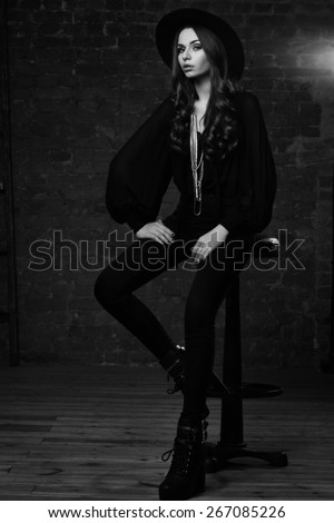 Fashion vogue style portrait of young pretty stylish sitting in loft interior on high barchair in black blouse, trousers, hat and boots