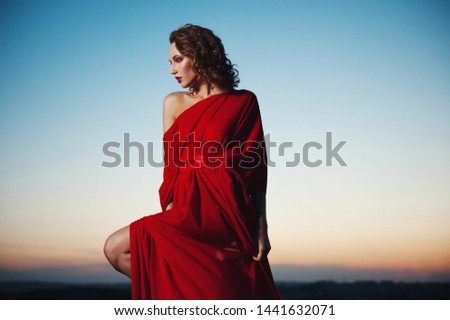 Fashion vogue style portrait of young stunning woman posing in red dress in sunset lightning. Gorgeous glamorous woman with dark curly hair