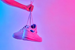 Fashion white sneakers in neon light. Sport shoes for training in the gym. Creative minimalism.
