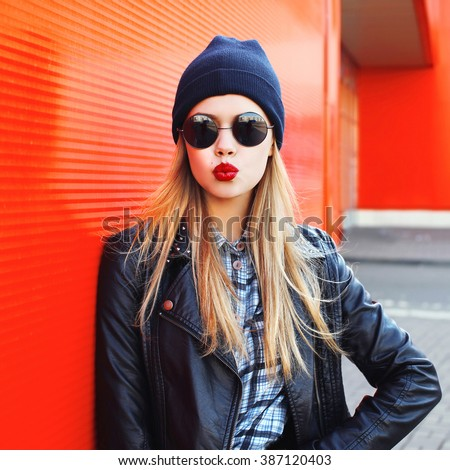 Stock Photo Fashion woman blowing lips with red lipstick wearing a rock black style having fun in city