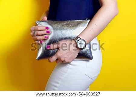 Fashion woman hold silver clutch in hand bag and watch near yellow background. Close up stylish accessory #564083527