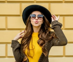 Fashion woman in a hat and sunglasses, in knit dress and jacket outdoors in the fall.Blowing lips kiss.
